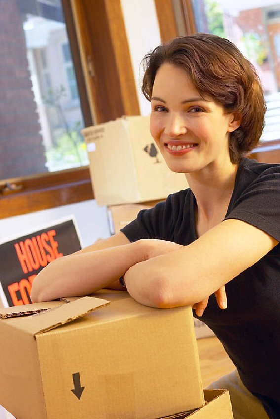Smiling woman moving into new house uid 1281108